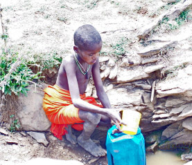Young boy collecting drinking water for his family's use in Northern Kenya